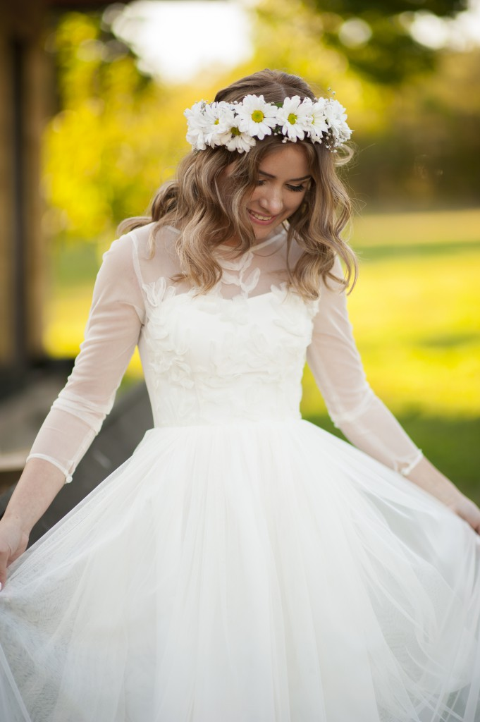 Smiling happy bride poses and enjoys her white dress and floral crown
